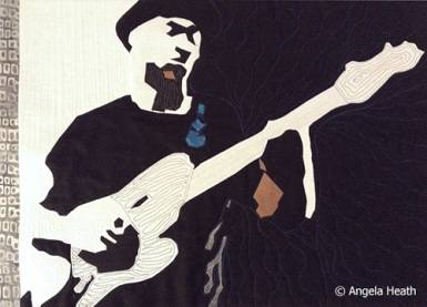GUITAR MAN; 20″w by 16″h; Fused applique, commercial Kona cotton. Quilted.